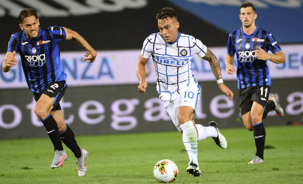 Inter Milan's Lautaro Martinez, foreground, controls the ball as Atalanta's Rafael Tolói chases, during a serie A soccer match between Atalanta and In...
