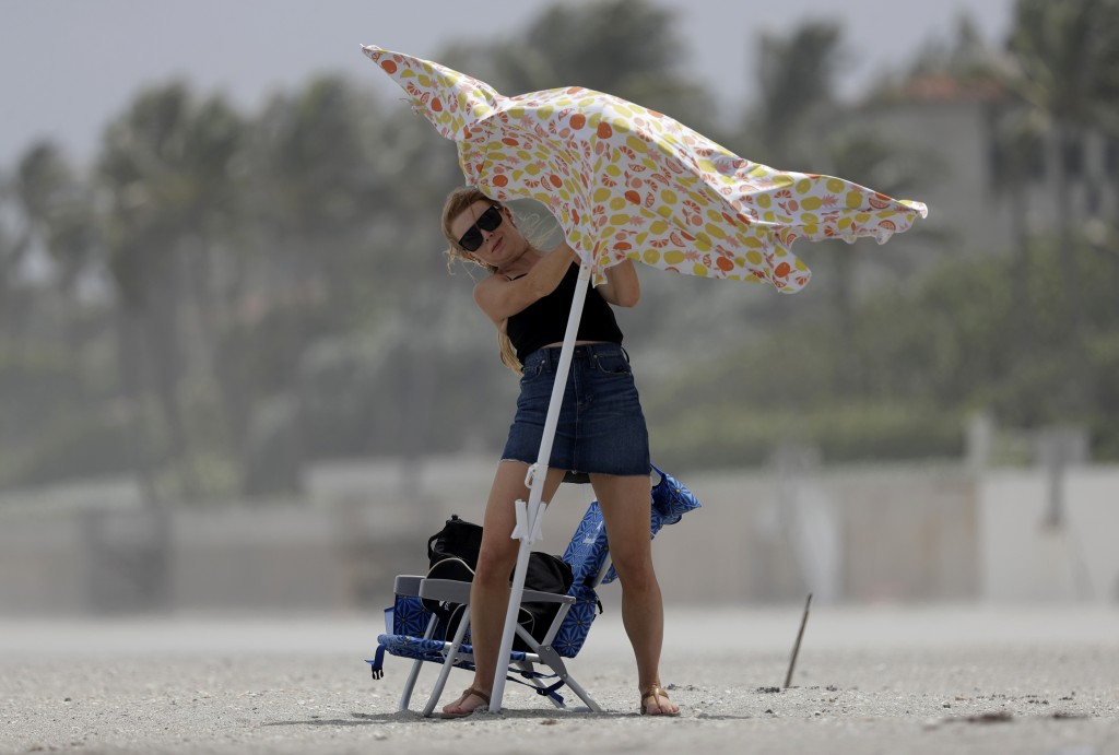 A beach goer attempts to set up a beach umbrella, Saturday, Aug. 1, 2020, in Palm Beach, Fla. Hurricane Isaias is headed toward the Florida coast, whe...