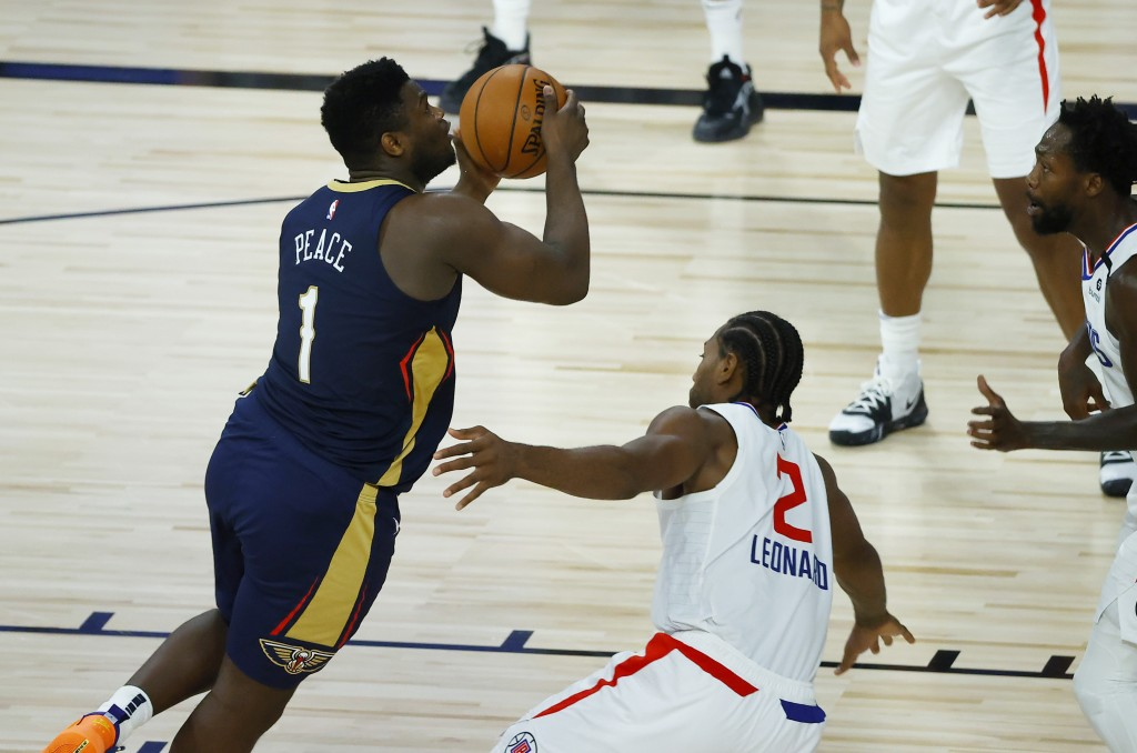 New Orleans Pelicans' Zion Williamson, left, drives to the basket against Los Angeles Clippers' Kawhi Leonard during an NBA basketball game Saturday, ...