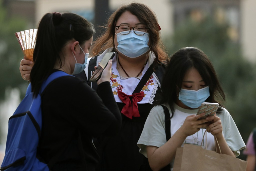 Women wearing face masks to protect against the new coronavirus browse their smartphones at a shopping mall in Beijing, Sunday, Aug. 2, 2020. (AP Phot...