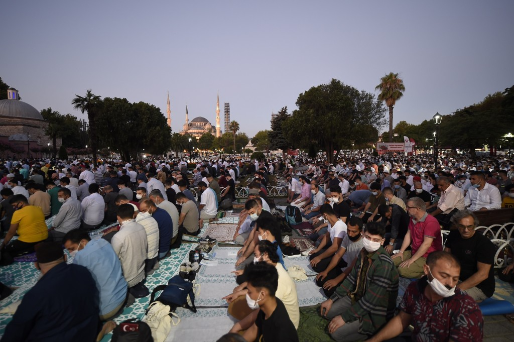 Muslims, wearing protective masks as a precaution against the coronavirus, offer their prayers during the Eid al-Adha prayer backdropped by the Byzant...