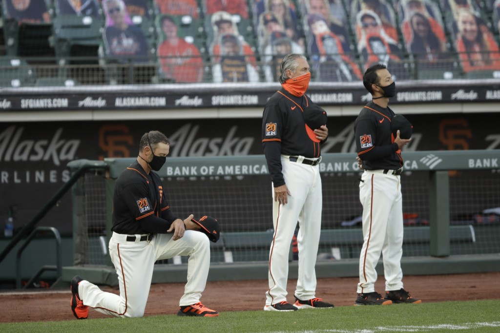 San Francisco Giants manager Gabe Kapler, left, kneels during the national anthem prior to the team's baseball game against the Texas Rangers on Satur...