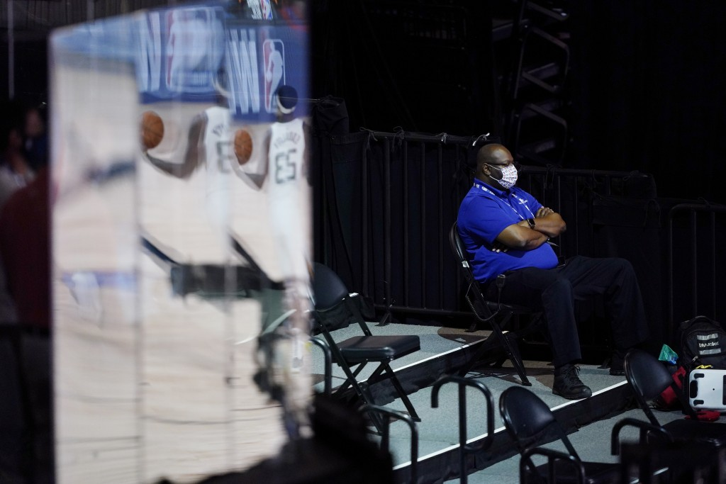 A man wearing a mask watches during halftime of an NBA basketball game between the Utah Jazz and the Oklahoma City Thunder, Saturday, Aug. 1, 2020, in...