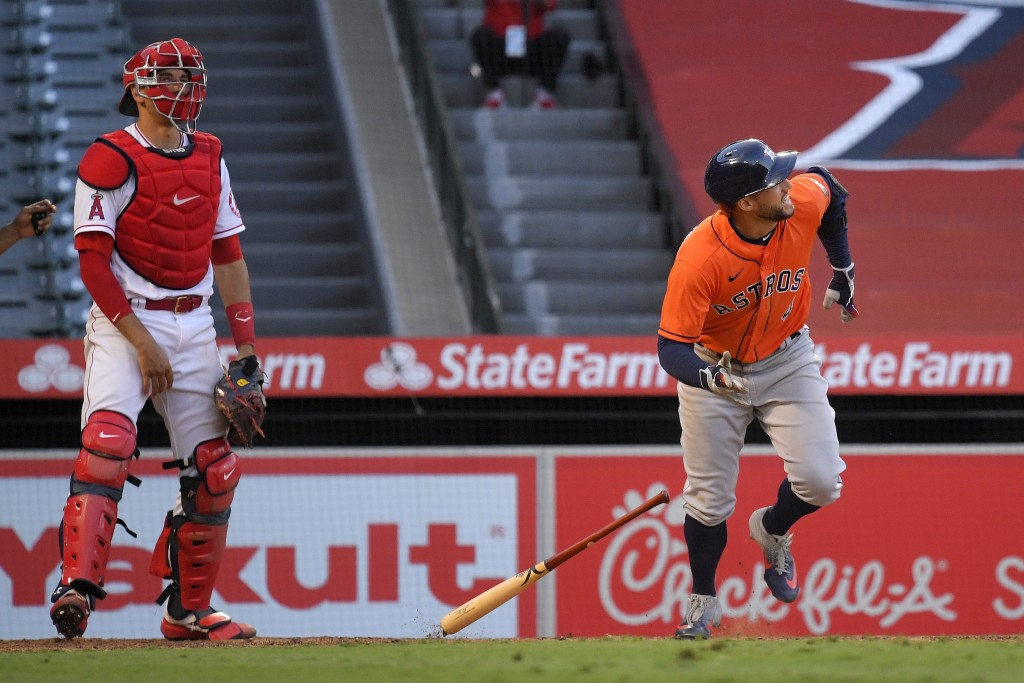 Houston Astros' George Springer runs to first after hitting a two-run home run, next to Los Angeles Angels catcher Max Stassi during the ninth inning ...