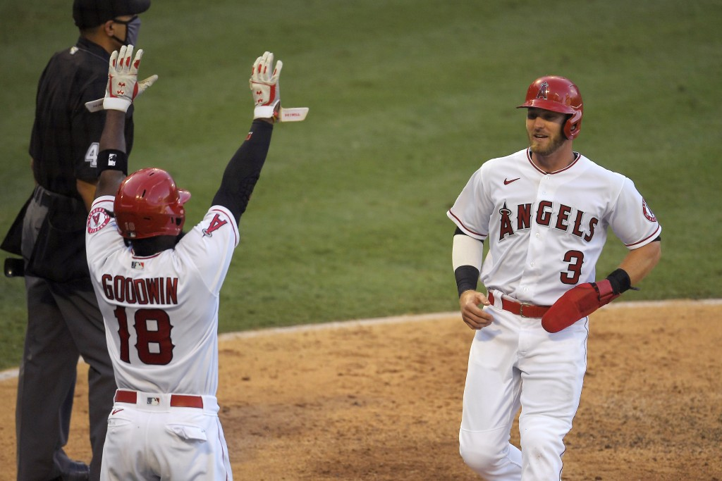 Los Angeles Angels' Taylor Ward, right, scores on a sacrifice fly hit by David Fletcher as Brian Goodwin (18) celebrates during the sixth inning of a ...