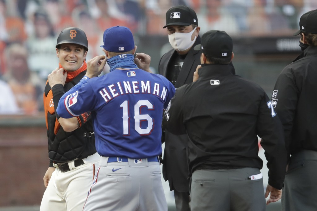 San Francisco Giants' Tyler Heineman, left, smiles at his brother Texas Rangers' Scott Heineman (16) as they represent with umpires prior to a basebal...