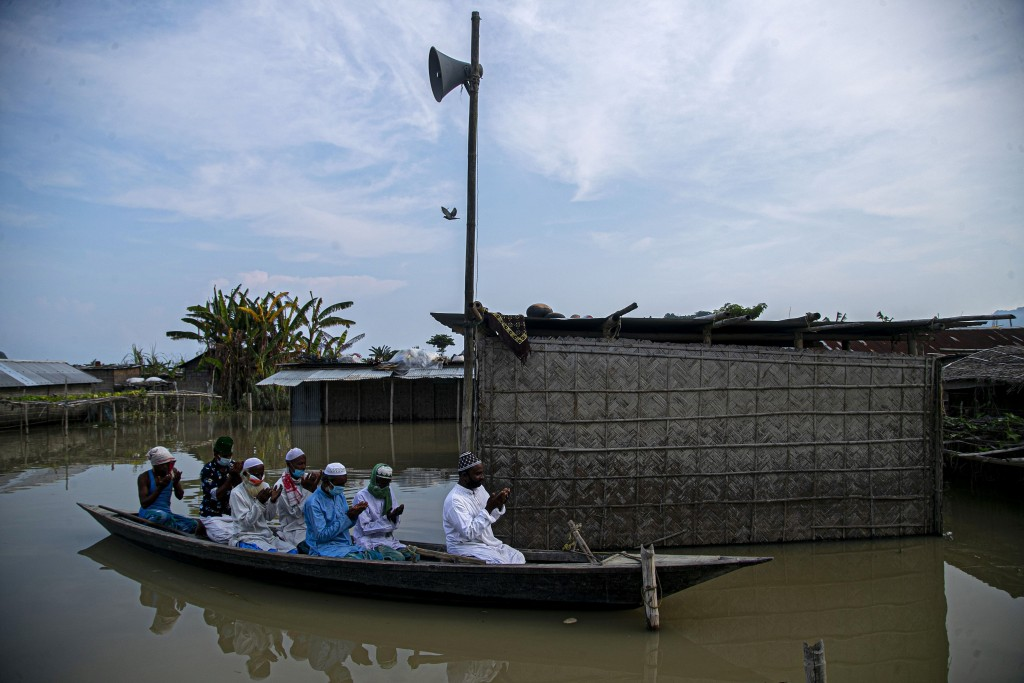 Flood affected Muslims offer Eid al-Adha prayers on a boat near a submerged mosque in Morigaon district of Assam, India, Saturday, Aug. 1, 2020. Musli...