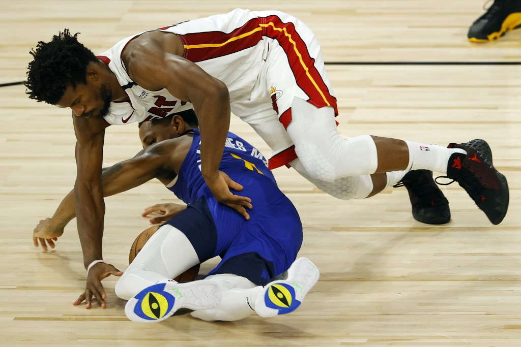 Denver Nuggets' Monte Morris, bottom, and Miami Heat's Jimmy Butler scramble for the ball during an NBA basketball game, Saturday, Aug. 1, 2020, in La...