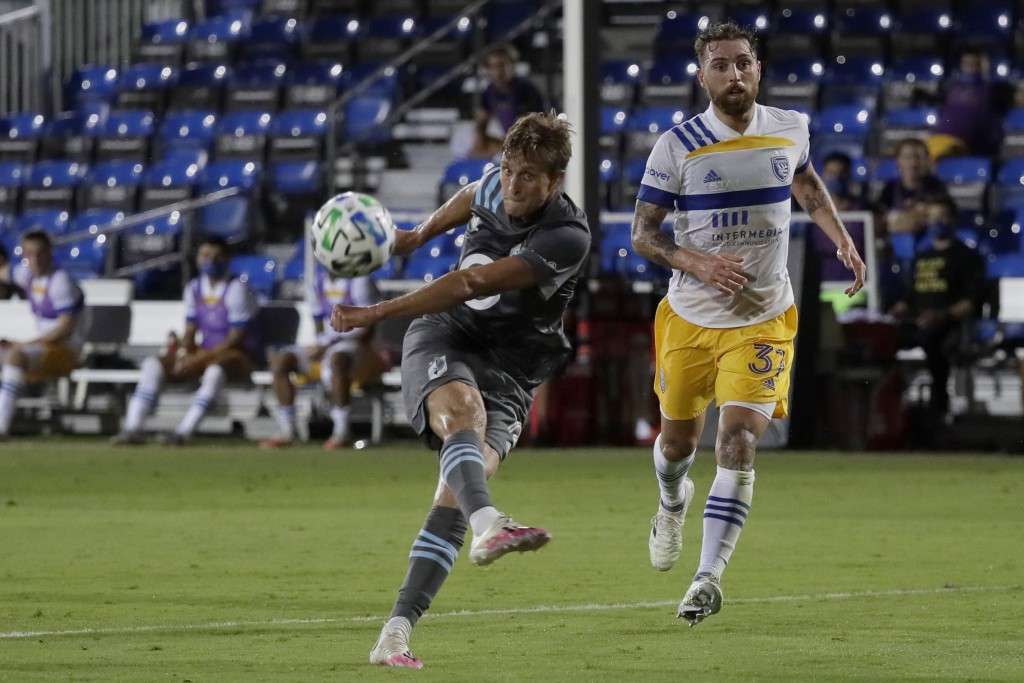 Minnesota United forward Aaron Schoenfeld, shoots as San Jose Earthquakes defender Guram Kashia looks on during the second half of an MLS soccer match...