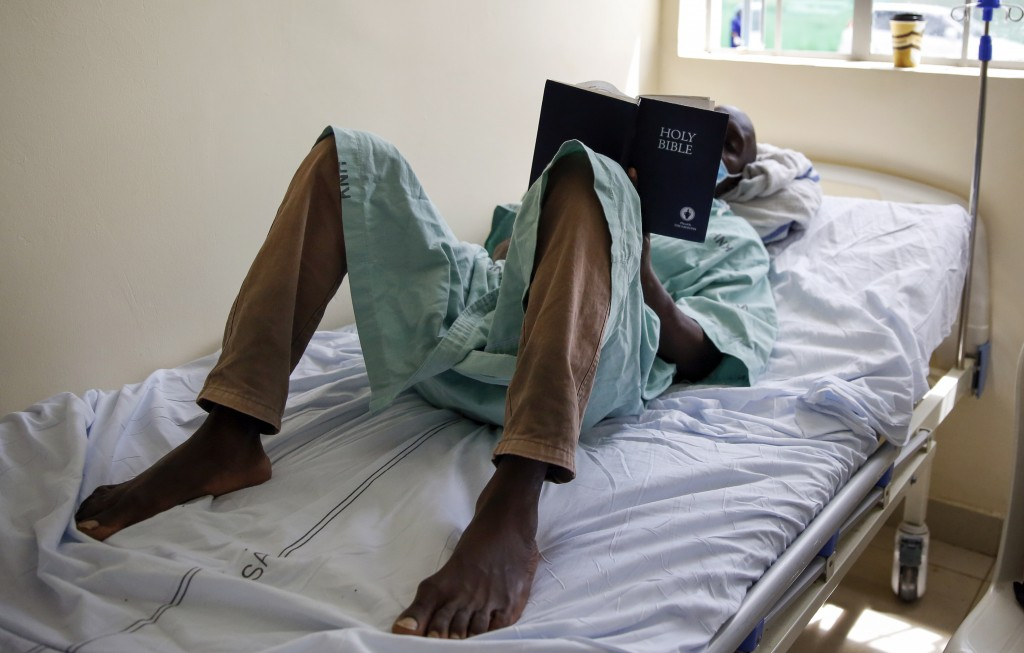 FILE - In this May 1, 2020, file photo, a patient lies on his bed reading the Bible in a ward for those who have tested positive for the new coronavir...