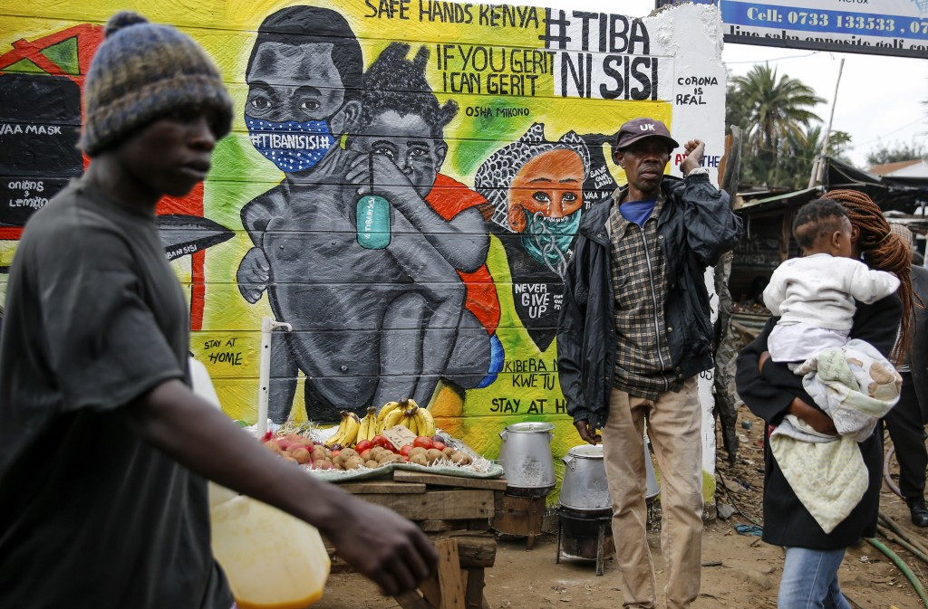 FILE - In this July 8, 2020, file photo, people walk past an informational mural warning people about the dangers of the new coronavirus and how to pr...