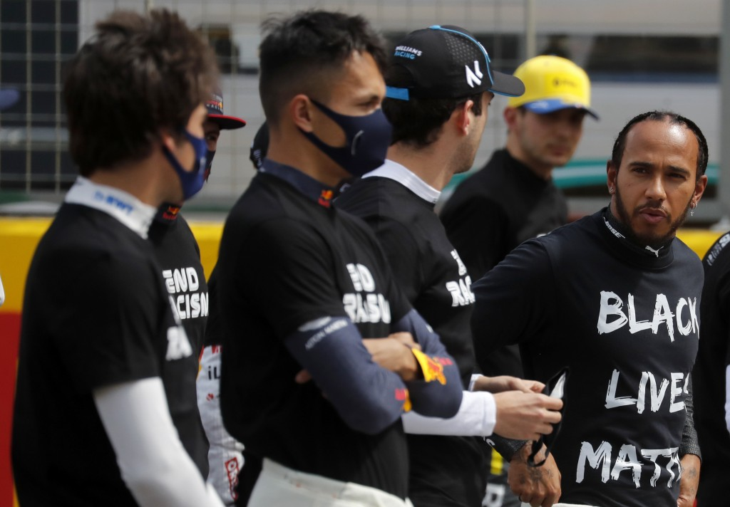 Mercedes driver Lewis Hamilton of Britain, right, and the drivers wearing a Black Lives Matter shirt, stand against racism in the pit lane prior the B...