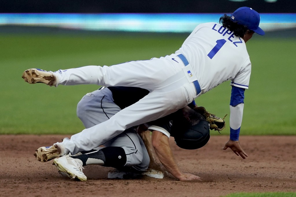 Kansas City Royals second baseman Nicky Lopez falls over Chicago White Sox's Adam Engel after forcing him out at second on a double play hit into by N...