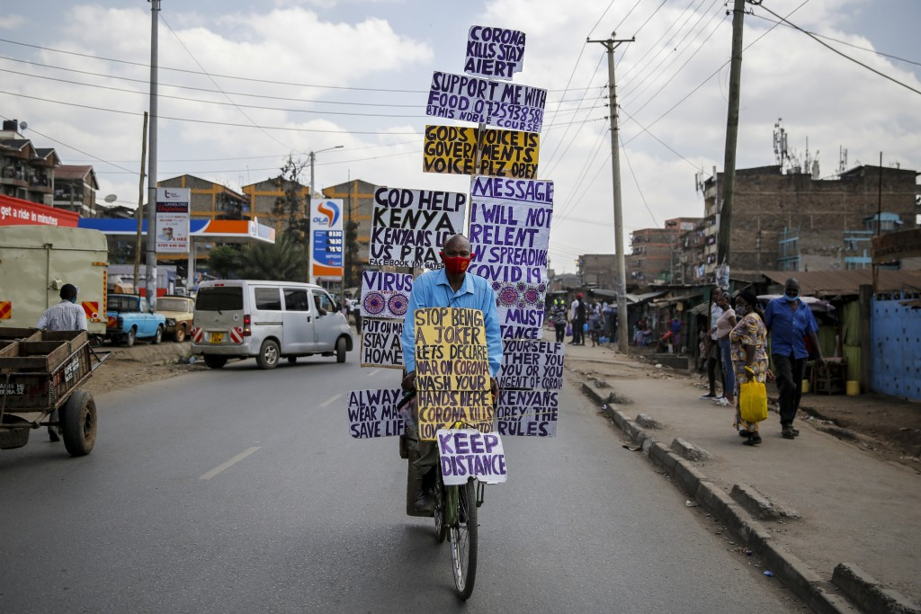 FILE - In this Thursday, May 28, 2020 file photo, Samson Waithaka rides a bicycle with informational messages warning about the new coronavirus in the...