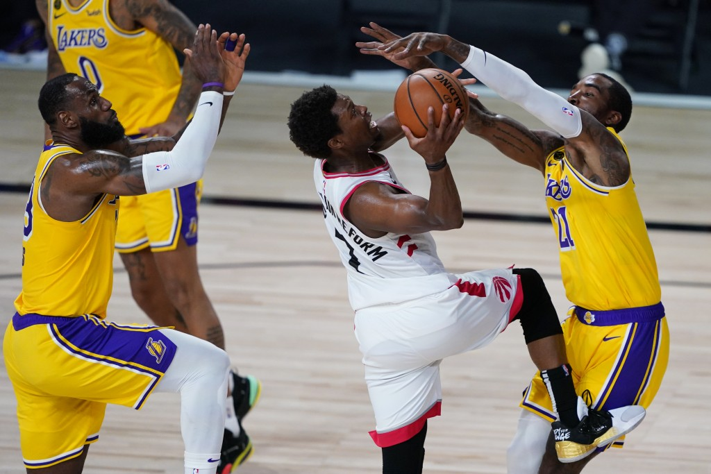 Los Angeles Lakers' LeBron James, left, and JR Smith, right, guard Toronto Raptors' Kyle Lowry during the second half of an NBA basketball game Saturd...