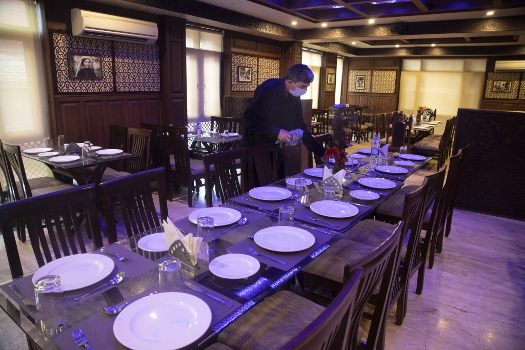 A Kashmiri waiter cleans a table inside a restaurant of Hotel Standard during lockdown to stop the spread of the coronavirus in Srinagar, Indian contr...