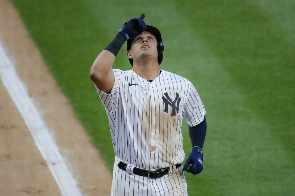 New York Yankees' Gio Urshela celebrates as he runs the bases after hitting a grand slam off Boston Red Sox starting pitcher Zack Godley during the se...