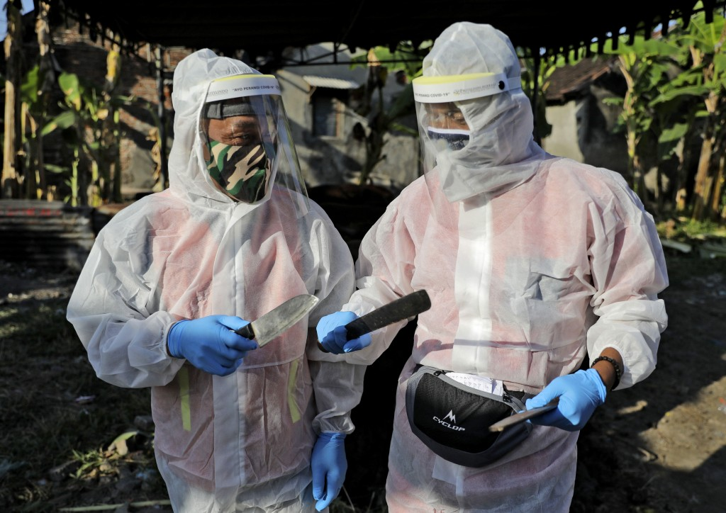 Butchers dressed in protective gear as a precaution against coronavirus outbreak sharpen their knives prior to slaughtering cows and goats during the ...