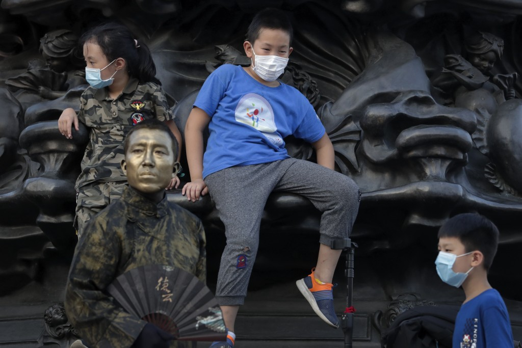 Children wearing face masks to protect against the new coronavirus play near a street performer dressed as a statue at a shopping mall in Beijing, Sun...