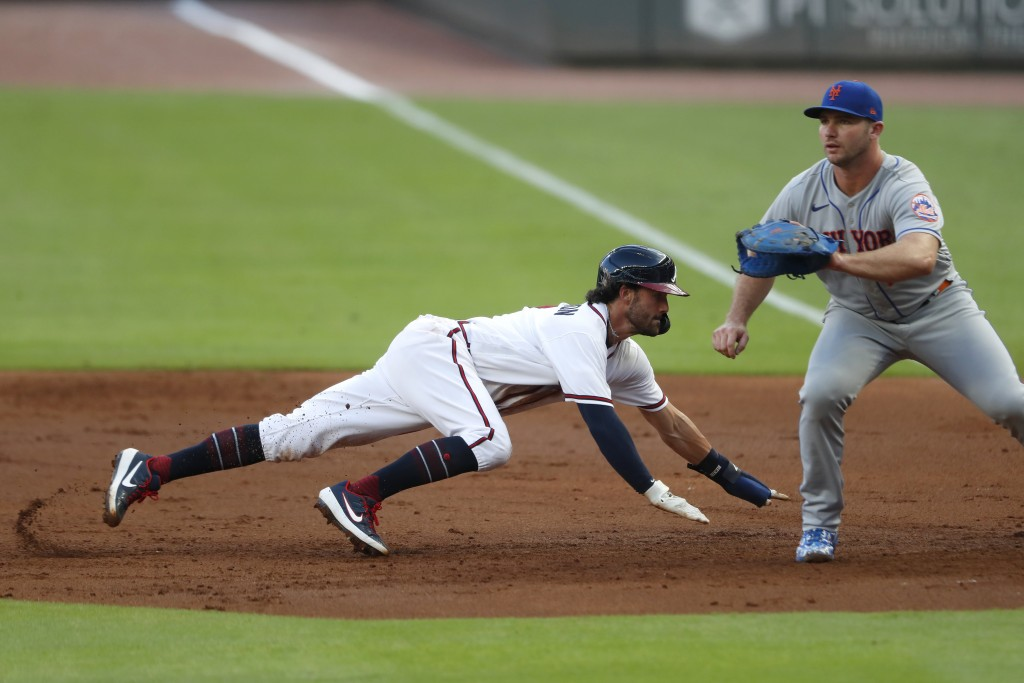 Atlanta Braves' Dansby Swanson, left, dives back to first base ahead of the throw to New York Mets first baseman Pete Alonso, right, in the second inn...