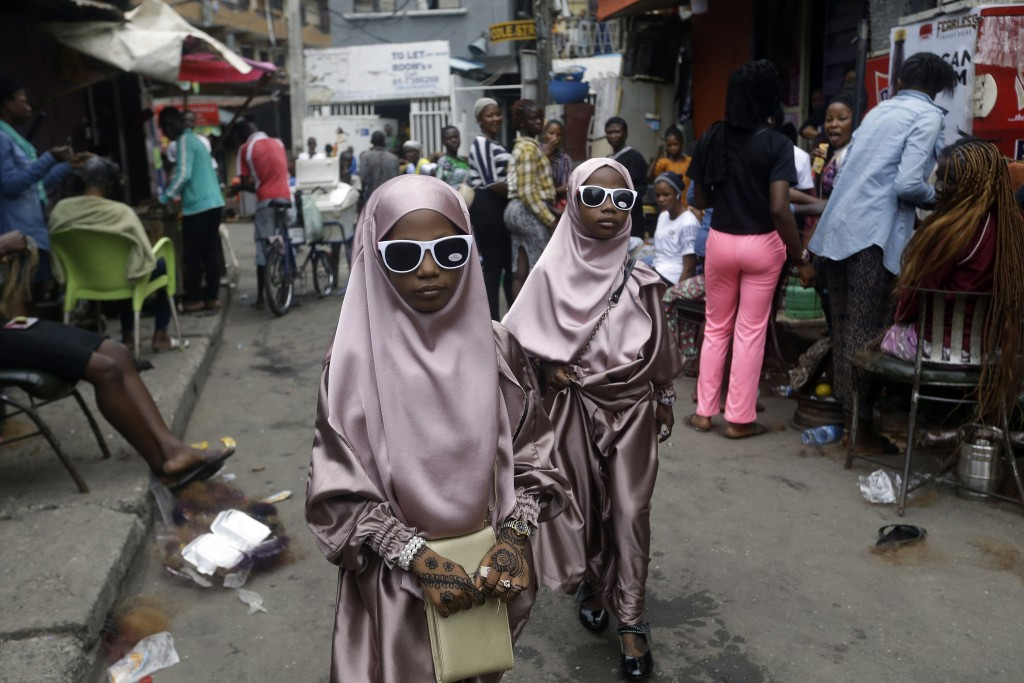 Muslim girls walk down a street after prayers, in Lagos, Nigeria, Friday, July 31, 2020. Small groups of pilgrims performed one of the final rites of ...