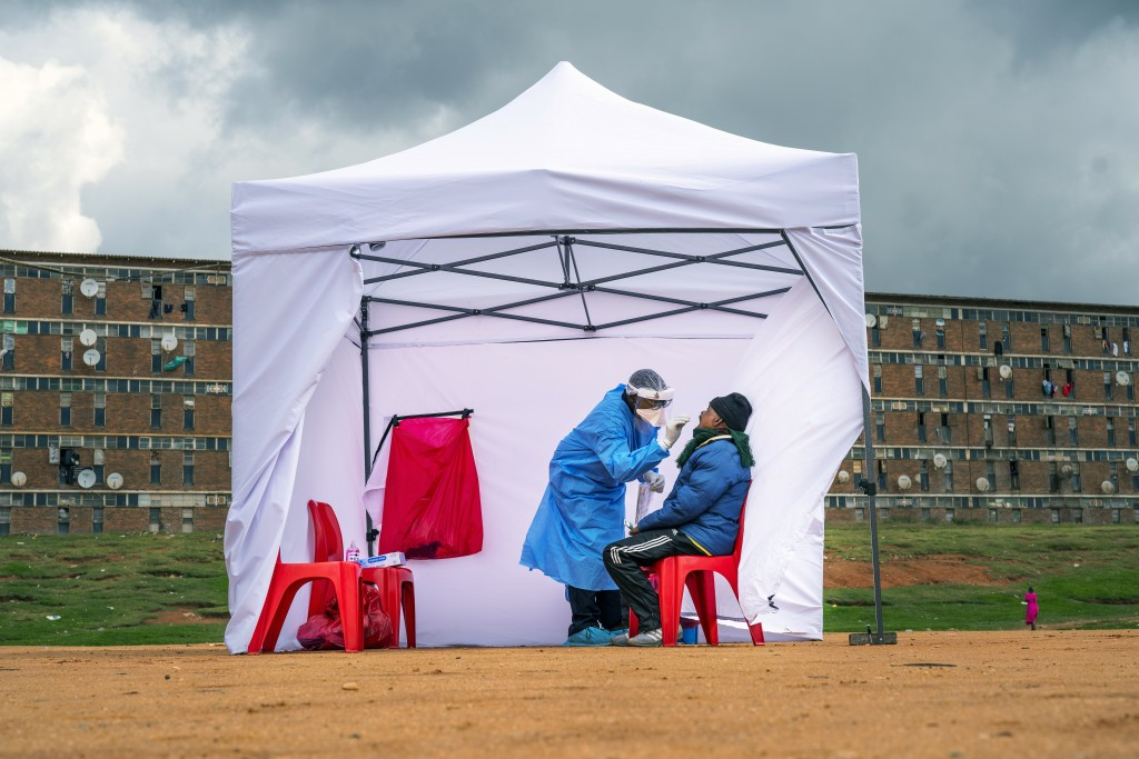 FILE - In this Wednesday, April 29, 2020 file photo, a resident from the Alexandra township gets tested for COVID-19 in Johannesburg, South Africa. A ...
