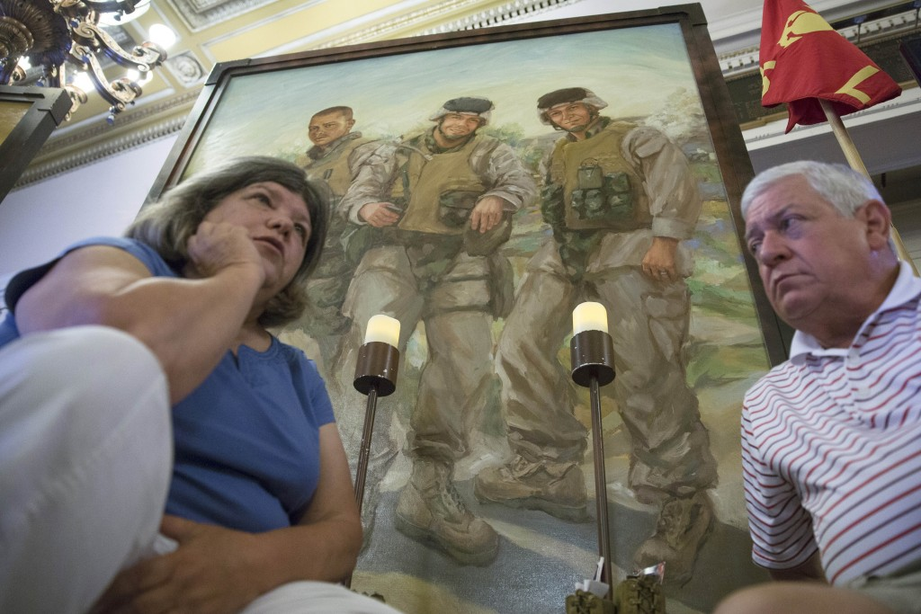 FILE—In this file photo from July 28, 2015, Pat Murray, left, and Ken Kreuter sit beneath a portrait of their son Marine Sgt. David Kreuter, top right...