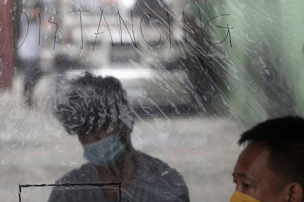 """A """"distancing"""" sign is placed on plastic sheets at a passenger jeepney terminal to help curb  the spread of COVID19 as drivers at the Tandang Sora sta..."""