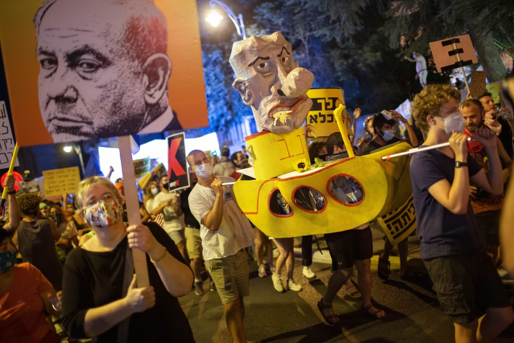 Demonstrators chant slogans and hold signs during a rally against Israel's Prime Minister Benjamin Netanyahu outside his residence in Jerusalem, Satur...