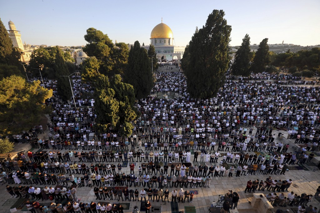 Muslim men offer Eid al-Adha prayer next to the Dome of the Rock Mosque in the Al Aqsa Mosque compound in Jerusalem's old city, Friday, July 31, 2020....