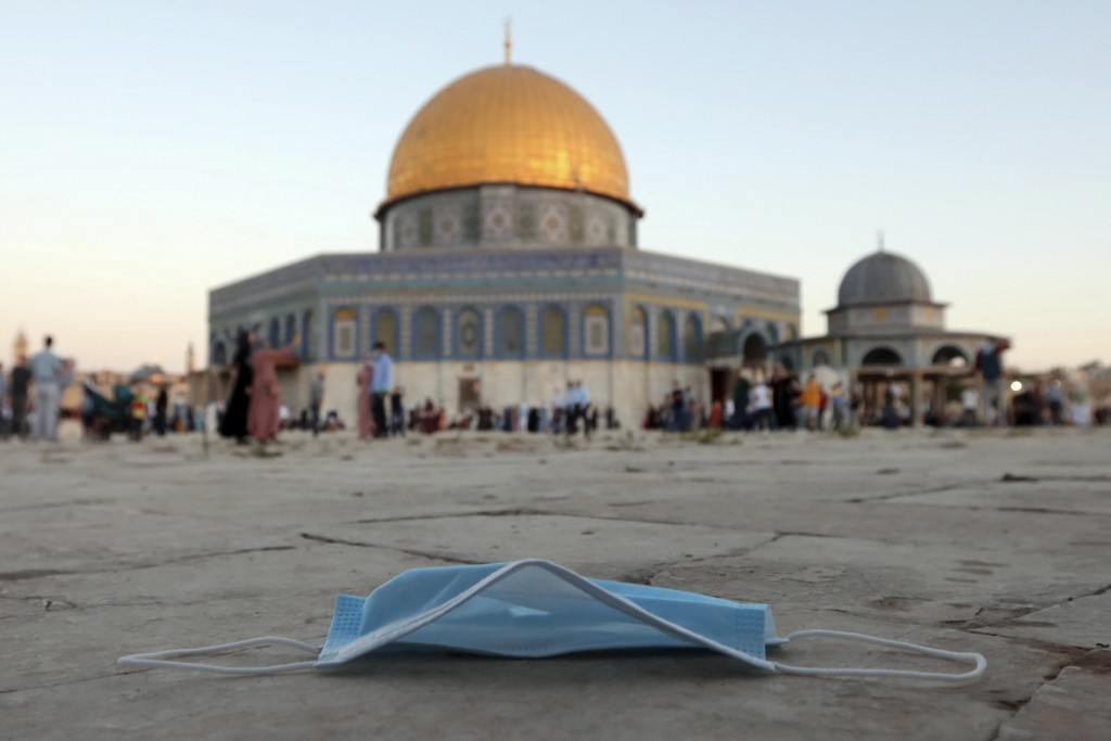 A protective face mask is thrown on the ground during Eid al-Adha prayer, next to the Dome of the Rock Mosque in the Al Aqsa Mosque compound in Jerusa...