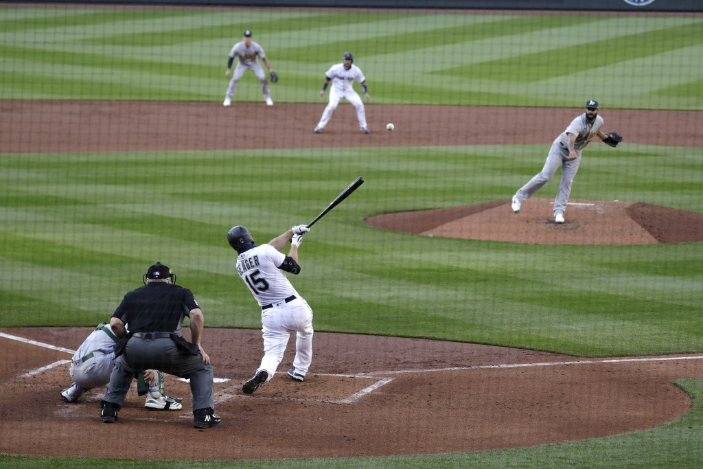Seattle Mariners' Kyle Seager (15) singles to drive in a pair of runs, as Oakland Athletics starter Mike Fiers follows through on his pitch during the...