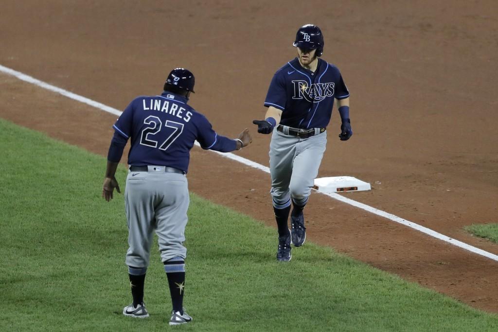 Tampa Bay Rays' Michael Brosseau, right, runs by third base coach Rodney Linares after hitting a solo home run off Baltimore Orioles starting pitcher ...