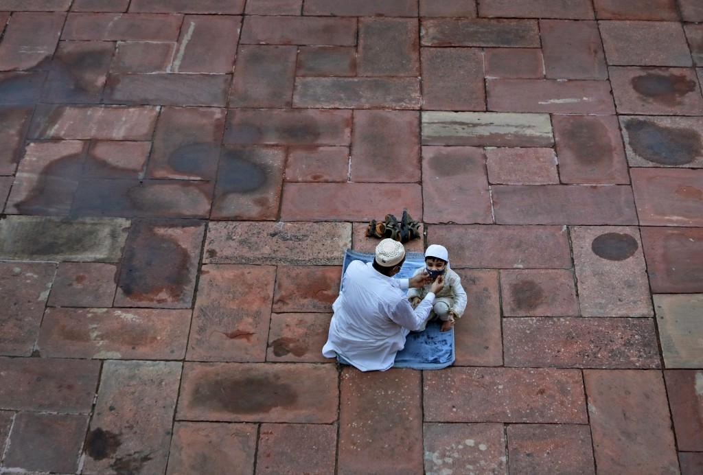 An Indian Muslim adjusts the mask of his son as they wait to offer Eid al-Adha prayer at the Jama Masjid in New Delhi, India, Saturday, Aug.1, 2020. M...