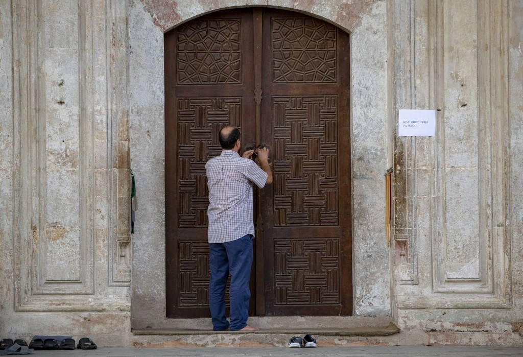 An employee of the Kosovo Islamic Community closes the door of the Sultan Mehmet Fatih mosque in Pristina, Kosovo, Friday, July 31, 2020. Government m...