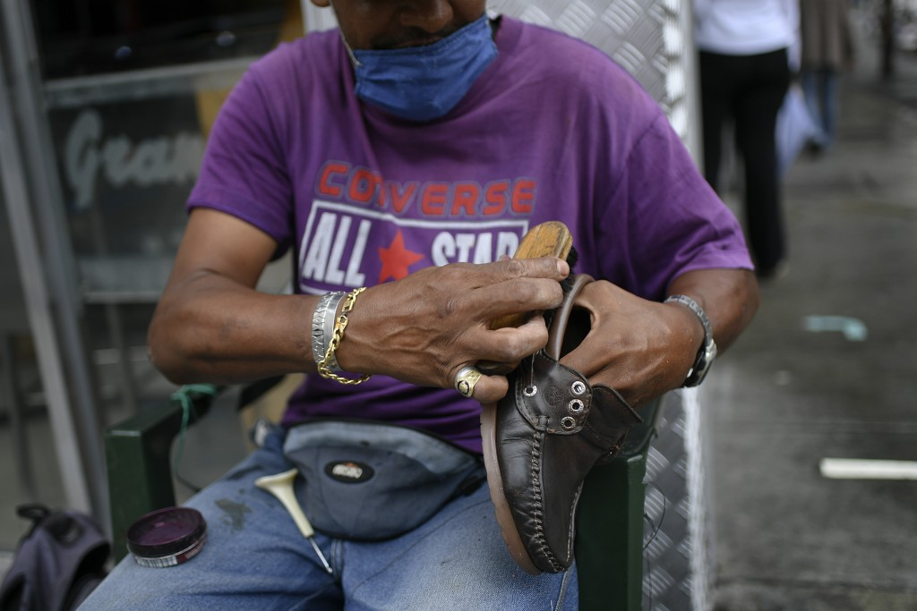 A shoeshiner, wearing a protective face mask, brushes a shoe on Sabana Grande boulevard in Caracas, Venezuela, Saturday, Aug. 1, 2020, amid the new co...
