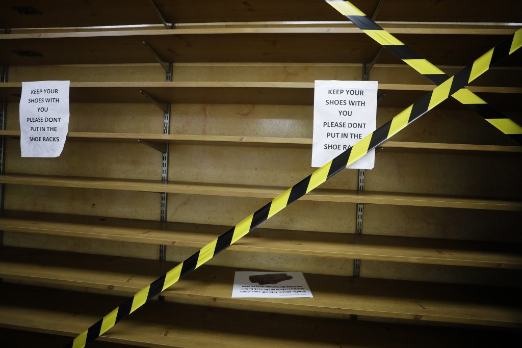 The shoe rack is taped off for safety measures at Minhaj-ul-Quran Mosque, at the start of Eid al-Adha, in London, Friday, July 31, 2020. Muslims world...