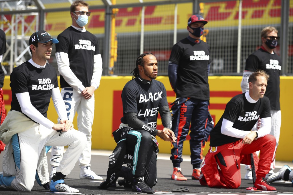Mercedes driver Lewis Hamilton of Britain, center and other drivers rivers kneel during the anti-racism demonstration ahead of the British Formula One...