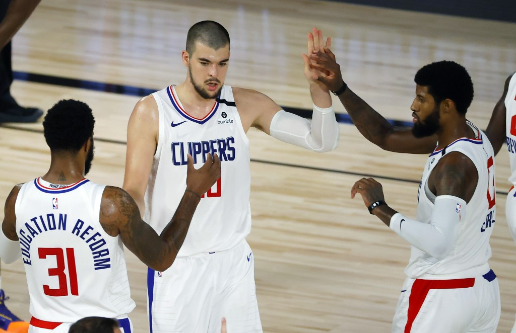 Los Angeles Clippers' Ivica Zubac, center, is congratulated by teammates Marcus Morris Sr. (31) and Paul George (13) during an NBA basketball game aga...