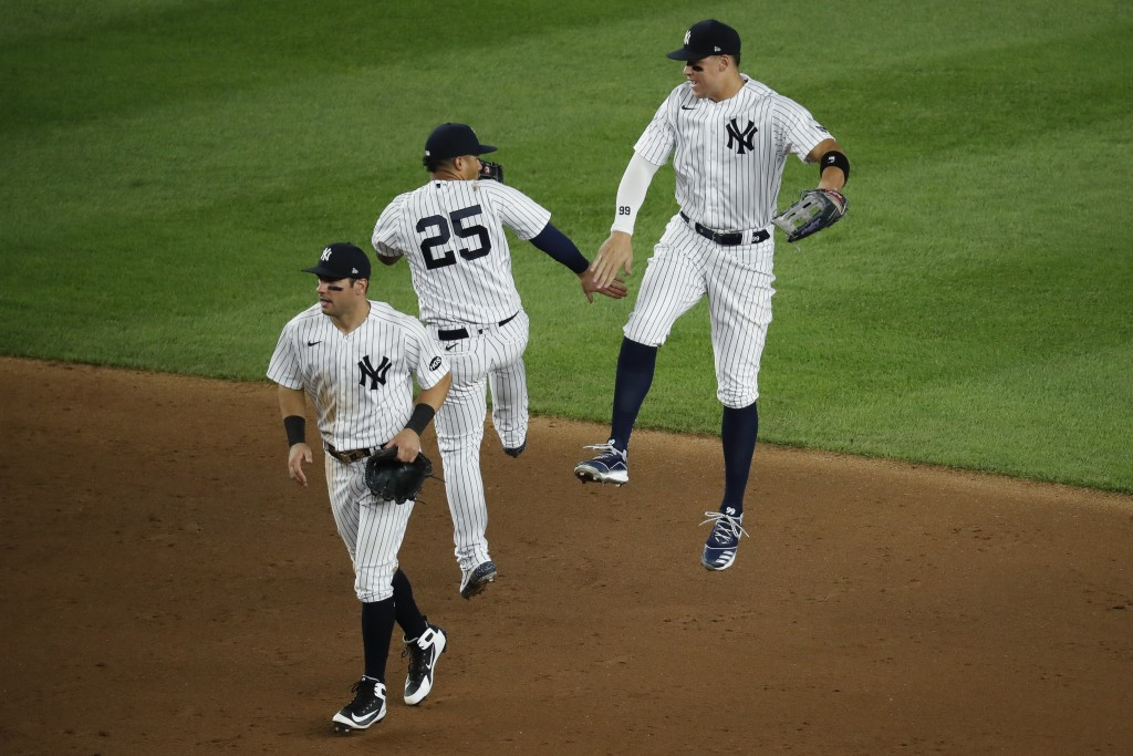 New York Yankees right fielder Aaron Judge (99) celebrates with second baseman Gleyber Torres (25) after closing the ninth inning of a baseball game a...