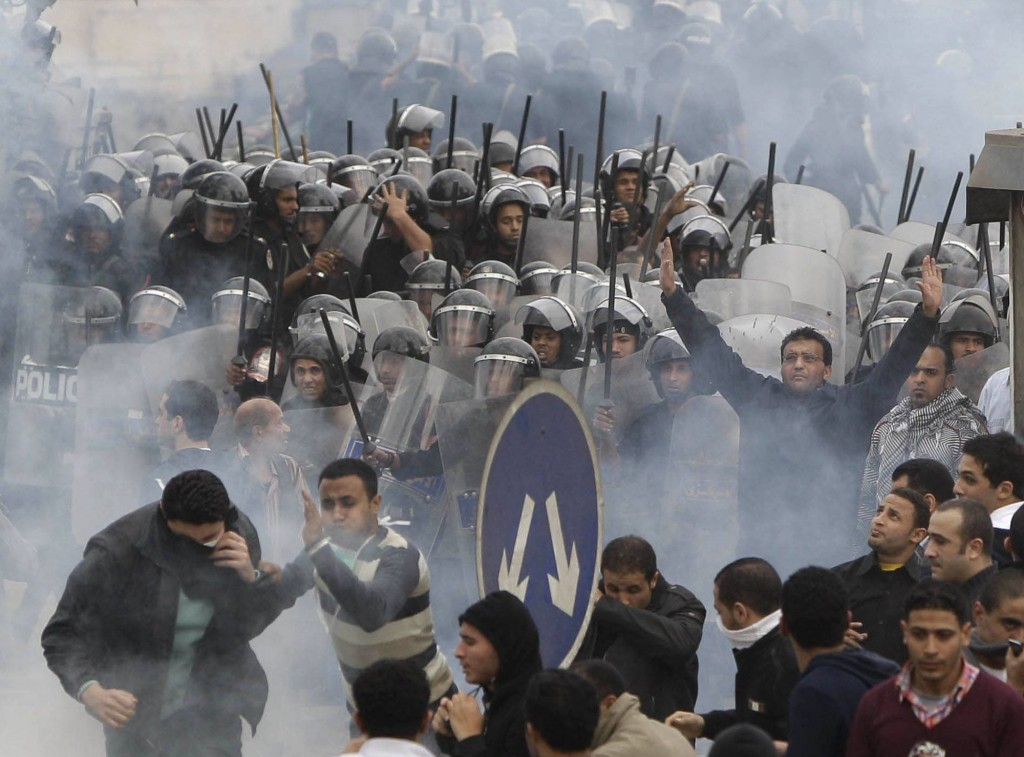 FILE - In this Friday, Jan. 28, 2011 file photo, anti-government activists clash with riot police in Cairo, Egypt, to challenge President Hosni Mubara...