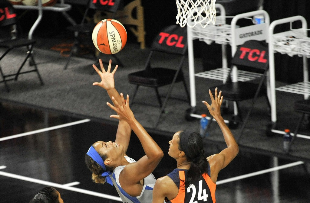 Minnesota Lynx's Napheesa Collier, left, shoots under pressure from Connecticut Sun's DeWanna Bonner during the first half of a WNBA basketball game S...
