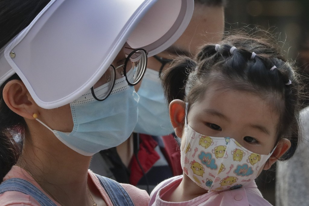 A woman and a child wearing face masks to protect against the new coronavirus visit a shopping mall in Beijing, Sunday, Aug. 2, 2020. (AP Photo/Andy W...