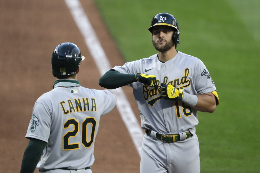 Oakland Athletics' Chad Pinder, right, is greeted by Mark Canha at home after hitting a two-run home run against the Seattle Mariners in the seventh i...