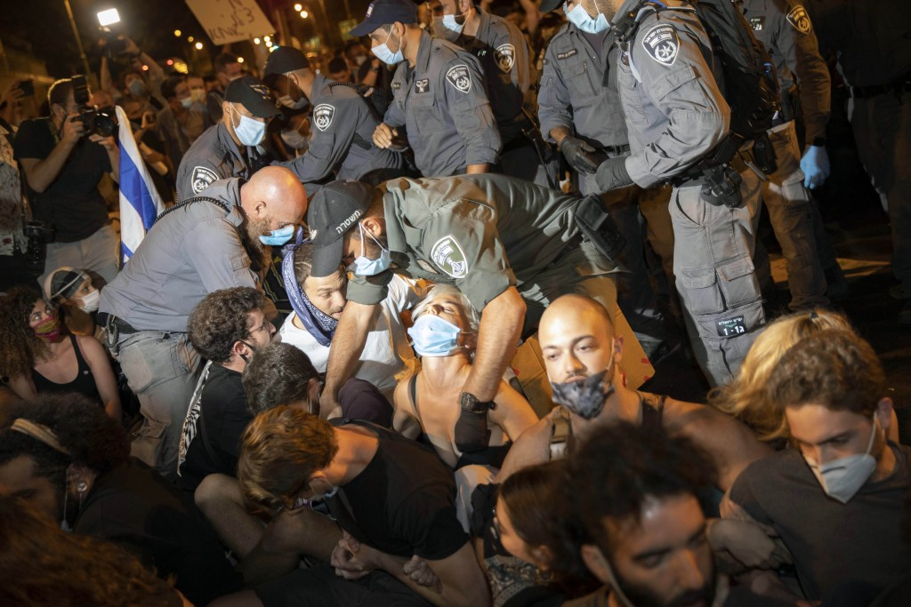 Police clear off protesters who blocked a main road during a protest against Israel's Prime Minister Benjamin Netanyahu outside his residence in Jerus...