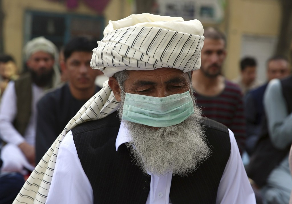 An Afghan Muslim man wearing a face mask as a precaution against coronavirus offers Eid al-Adha prayers in Kabul, Afghanistan, Friday, July 31, 2020. ...