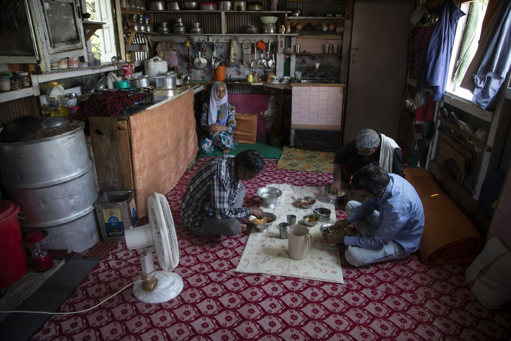 Kashmiri man Ghulam Qadir Ota and family members eat a meal inside their house boat during lockdown to stop the spread of the coronavirus at a Nigeen ...