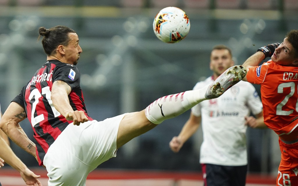 Milan's Zlatan Ibrahimovic, left, goes for the ball against Cagliari during a Serie A soccer match at the Giuseppe Meazza stadium in Milan, Italy, Sat...