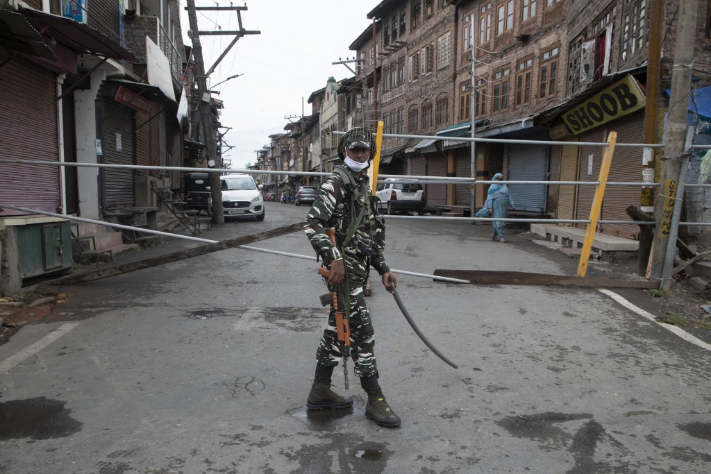 An Indian paramilitary soldier stands guard by a closed road, as Kashmiris marked Eid during lockdown to curb the spread of coronavirus in in Srinagar...