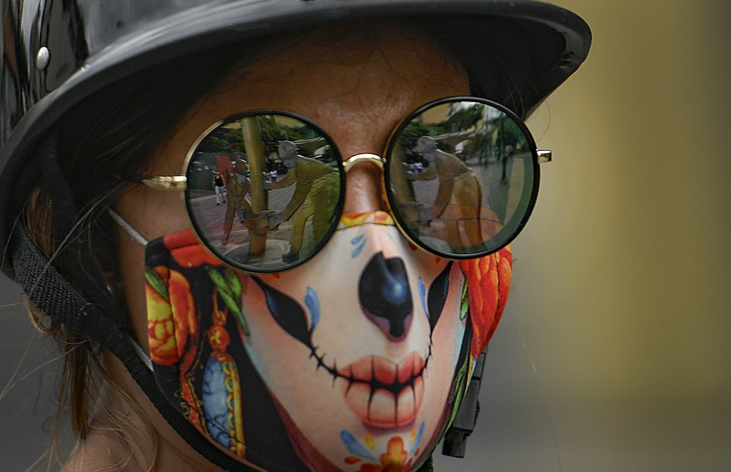 """The """"Oilworkers"""" sculpture by Beatriz Blanco is reflected in the sunglasses of a woman wearing a stylized protective face mask as a precaution against..."""